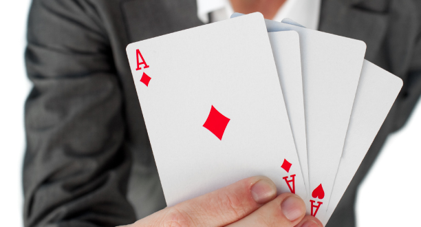 A person holding cards with the ace of diamonds showing.
